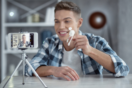 My new hobby. Attractive exuberant young well-built man smiling and holding a little skeleton in his hand while making a video 스톡 콘텐츠