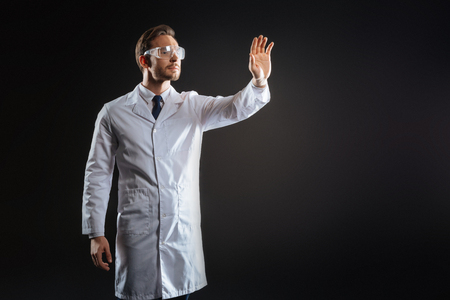 Personal task. Skilled smart handsome scientist standing in the dark room holding hand up and working.