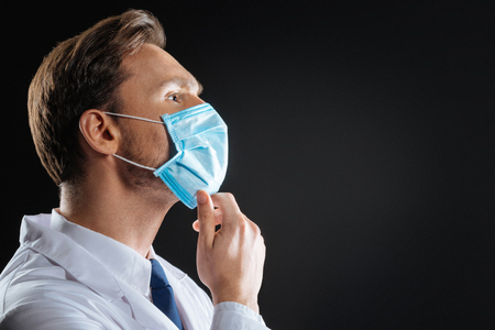Task for expert. Deep attentive responsible medic being in the dark room in a gauze mask looking up and thinking.