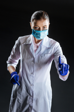 Continue your job. Focused occupied skilled medic in a gauze mask standing in the dark room looking aside using invisible gadget. Foto de archivo