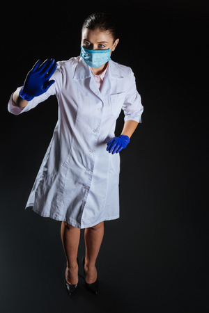 Bad variant. Occupied loaded perspective nurse standing in the dark room working on the project and holding hand up. Stock Photo