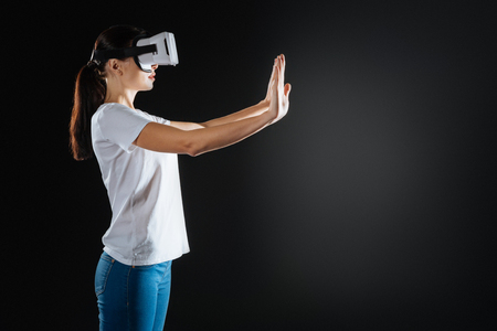 Advanced technologies. Concentrated interested cute woman standing in the empty room holding hands opposite herself and tasting VR glasses. Stock Photo