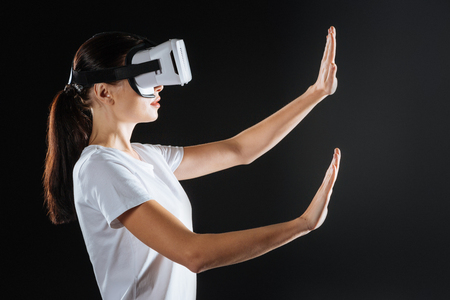 Modern entertainment. Cute interested smart woman standing in the dark room holding hands up using VR glasses.
