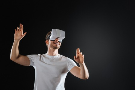 Unexpected result. Surprised handsome interested man standing in the empty room using VR glasses and smiling. Stock Photo