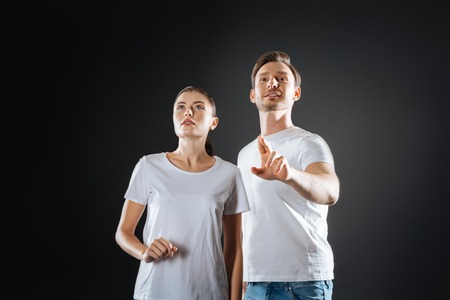 Like-minded couple. Stylish pretty sociable couple standing in the empty room looking up and dreaming. Stock Photo