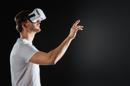 Intenta tocar. Ocupado, impresionado, hombre inquebrantable mirando a través de las gafas de realidad virtual en la espaciosa habitación y levantando la mano derecha. Foto de archivo