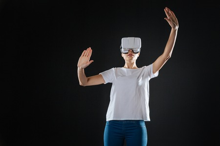New feeling. Occupied interested creative woman standing in the dark room holding hands up and tasting VR glasses. Stock Photo