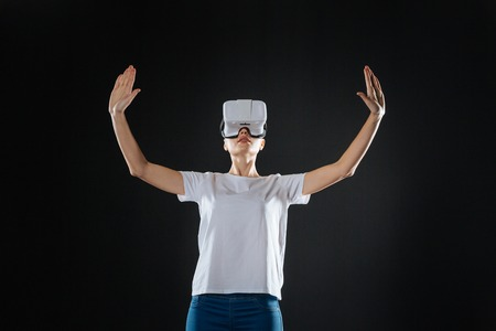 Impressed experience. Creative cute clever woman spending time in the empty room holding hands up and examining VR glasses.