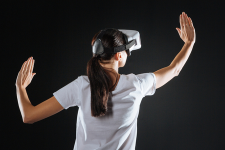 In another world. Interested impressed creative woman standing in the empty room using the VR glasses lifting right hand.