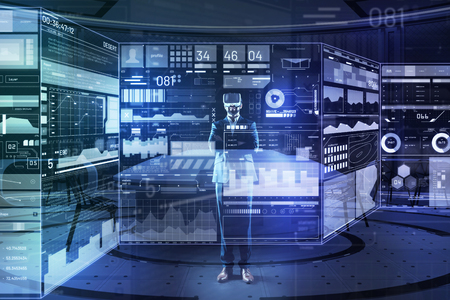 New view. Clever enthusiastic cheerful programmer standing in front of a giant transparent screen with his arms crossed and smiling while wearing virtual reality glasses