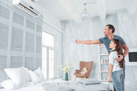 Air conditioning. Positive delighted joyful man standing together with his daughter and looking at the air conditioner while holing a remote control