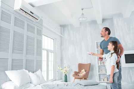 Climate control. Joyful positive nice girl standing together with her father and holding a remote control while turning on the air conditioner Stock Photo