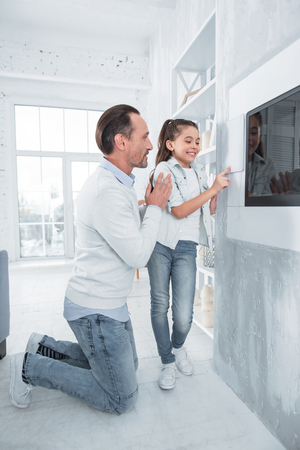 Do not worry. Nice positive handsome man standing near his daughter and helping her while teaching how to use smart home technology Imagens