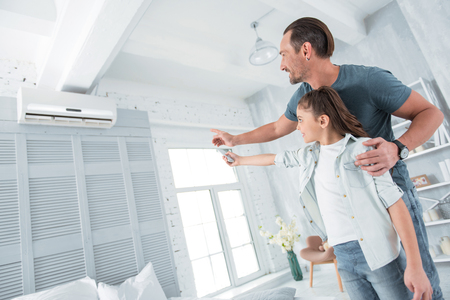Comfortable temperature. Positive happy joyful man standing near his daughter and pointing at the air conditioner while teaching her how to use it Stock fotó