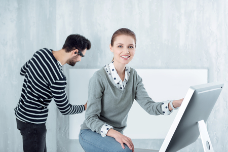Feeling good. Positive delighted female keeping smile on her face and putting right arm on knee while standing near computer