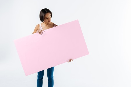 Young activist. Smart serious young woman holding a pink poster and looking at it while standing against white background