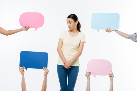 What is this. Nice surprised young woman standing against white background and looking at the sign while being curious what is this Stock Photo