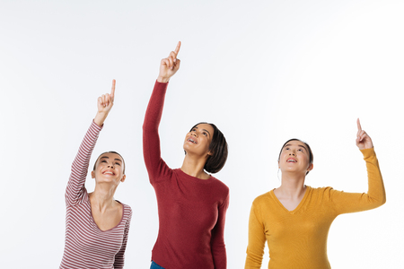 Over there. Joyful positive nice women smiling and holding their arms up while pointing with their fingers
