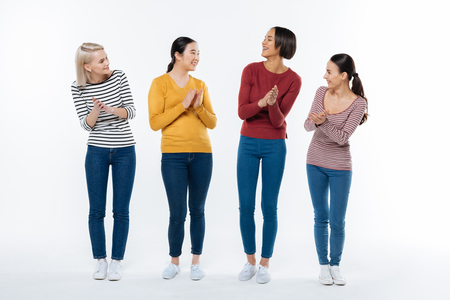 Female support. Positive joyful happy women looking at each other and applauding while expressing their support Stock Photo