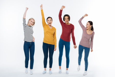 Our achievement. Joyful nice attractive women standing together and saying yes while being happy about their achievement Stock Photo