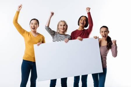 Female team. Positive nice cheerful women holing a poster and looking at you while being a team Stock Photo