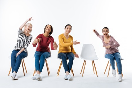 Come to us. Joyful nice happy women smiling and pointing at the chair while inviting you to them