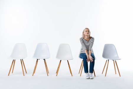 Being bored. Pleasant nice young woman sitting on the chair and waiting for her friends while being bored