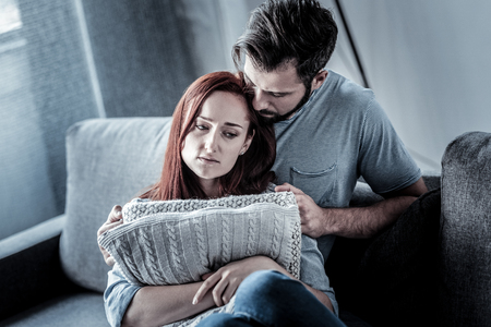 Im so sorry. Upset exhausted redhead woman sitting on the sofa near her husband looking aside and hugging pillows. 写真素材