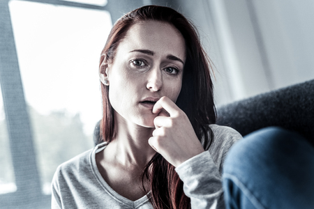 Im in trouble. Depressed upset redhead woman feeling bed herself holding hand near mouth and looking straight.