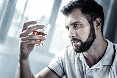 Im alone. Sad upset beardful man spending time alone in the bright room holding and looking at the glass of alcohol.