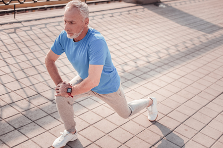 I can. Serious aged focused man preparing for the training looking straight making stretch exercises. Foto de archivo