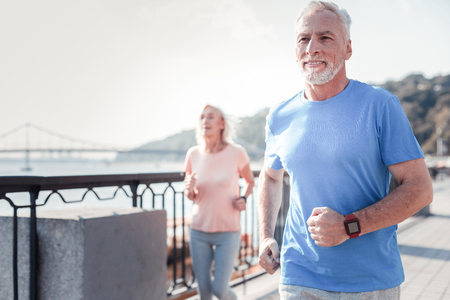 Life is good. Satisfied athletic unshaken man spending time on fresh air looking straight and having cardio exercises on the quay.