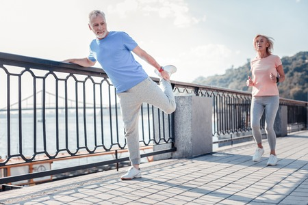 Sport for everyone. Satisfied unshaken senior man spending time on fresh air holding by the railing doing stretching exercises.
