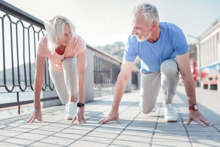 Competencia amistosa. Alegre pareja agradable senior tocando el suelo sonriendo y preparándose para correr por el muelle. Foto de archivo