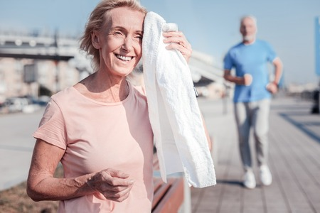 Productive training. Satisfied senior athletic woman being on the street smiling and wiping with a towel.
