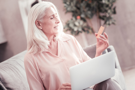 Useful thing. Occupied concentrated aged lady sitting on the sofa holding the laptop on her knees and overlooking the credit card.
