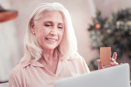 Pay online. Interested satisfied elderly woman spending time at home looking at the screen of the laptop and holding credit card.