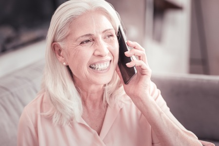 Nice to hear you. Satisfied aged cute woman sitting at home in the bright room having conversation and laughing. Stock Photo