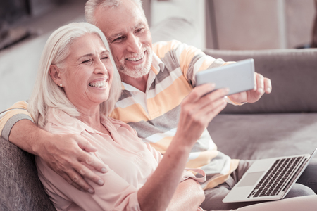 Make a selfie. Happy senior funny couple sitting on the sofa with the laptop laughing and making photo on frontal camera of the smartphone.