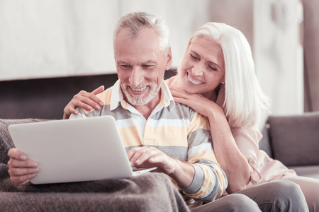 Funny moments. Interested aged pleasant couple spending time together at home smiling and working with the laptop.