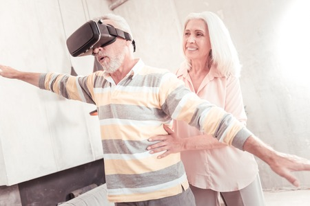 Like a bird. Senior interested smart man standing in the specious room holding hands up and looking through the VR glasses.