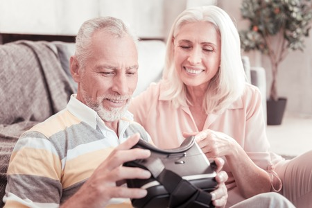 Modern technologies. Interested aged cute couple sitting on the sofa overlooking VR glasses focusing on it. Stock Photo