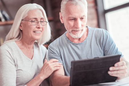 Modern retirements. Smart interested aged couple sitting by the table smiling and looking at the tablet. Standard-Bild - 97820882