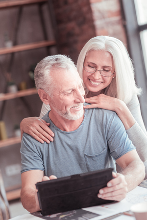 You will do this. Handsome aged smart man sitting by the table spending time with his wife and using the tablet. Stock fotó
