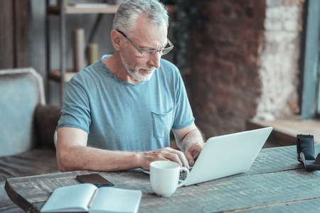 Full concentration. Serious bespectacled aged man sitting in the room by the table having important task and working with the laptop. Stock Photo