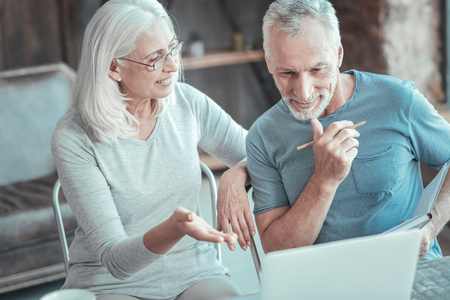 What do you think. Pleasant busy senior couple working together with the laptop communicating and thinking about the task. Stock Photo