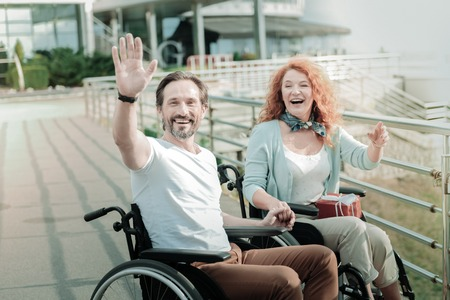Hey you. Positive disabled woman keeping smile on her face and holding present on knees while holding hand on her boyfriend