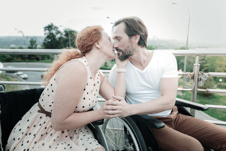 Sweet kiss. Happy bearded sitting on his wheelchair and turning head while looking at his girlfriend