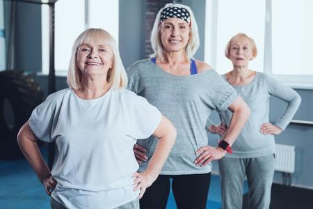 Der Ruhestand ist nicht das Ende. Strahlende reife Frauen, die die Kamera bei der Stellung mit ihren Händen auf den Hüften untersuchen und eine Übungsklasse nehmen. Standard-Bild - 97821826