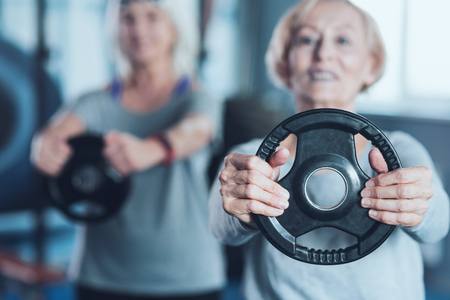 Getting better and stronger. Selective focus on a weight disk held by a motivated senior woman training in a gym and doing weight exercises during a group training class. Stock Photo
